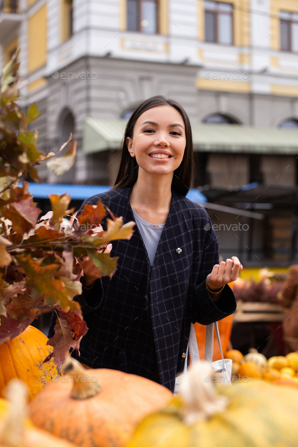 Young cheerful casual woman happily looking in camera at autumn farm shop outdoor - Stock Photo - Images