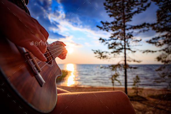 Woman at sunset holding a ukulele - Stock Photo - Images
