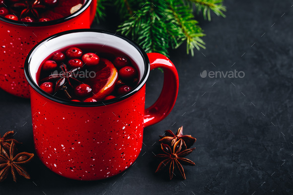 Traditional Christmas Mulled Wine drink with cranberries, orange slices and spices in red mugs - Stock Photo - Images