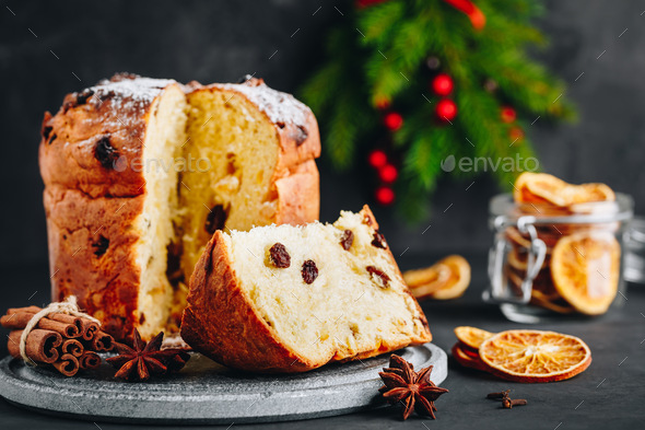 Traditional Christmas Panettone cake with dried fruits on dark stone background - Stock Photo - Images