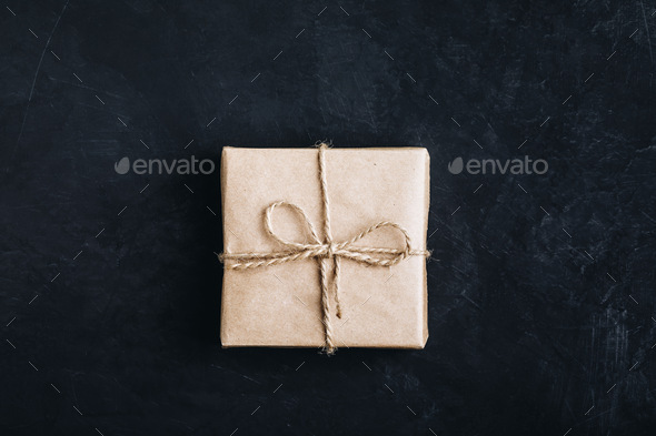Christmas gift box. Christmas present in paper box on dark stone background. Top view - Stock Photo - Images