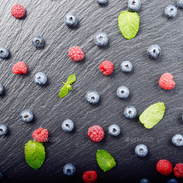 Flat lay view at ripe bilberry and raspberry berries on slate st - Stock Photo - Images