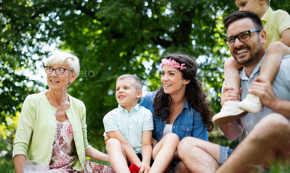 Happy family playing and enjoying picnic with children outside - Stock Photo - Images