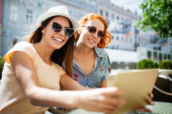 Friends and tourism concept. Beautiful girls having fun together in cafe - Stock Photo - Images