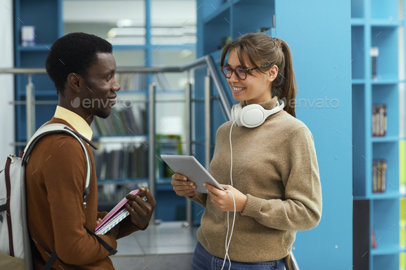 Students Chatting in School Library - Stock Photo - Images