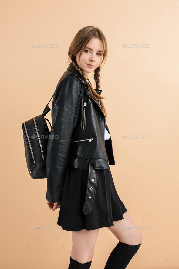 Young smiling school girl with braids in leather jacket and skirt happily looking in camera - Stock Photo - Images