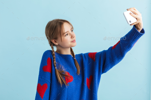 Young beautiful girl with two braids in navy color sweater happily taking selfie on cellphone - Stock Photo - Images