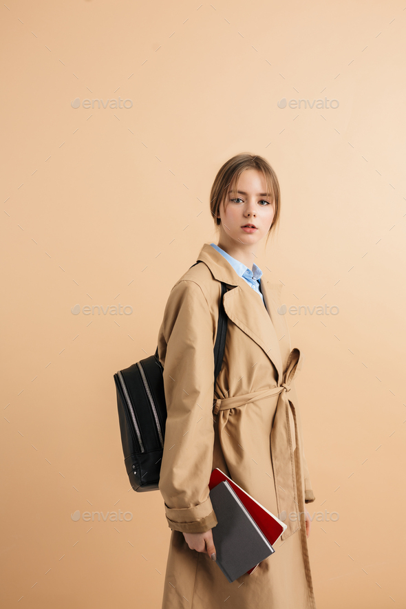 Young beautiful school girl in trench coat thoughtfully looking in camera - Stock Photo - Images