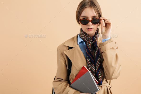 Young stylish dreamy girl in trench coat and sunglasses with notepad curious looking in camera - Stock Photo - Images