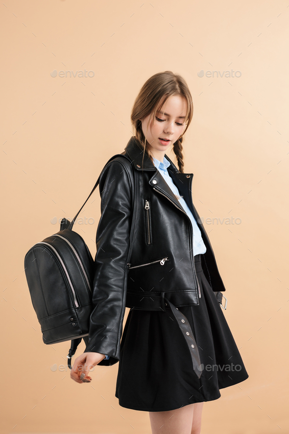 Young beautiful girl with braids in leather jacket and skirt with backpack dreamily dancing - Stock Photo - Images