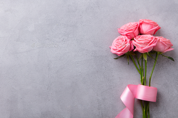 Pink Roses with Pink Ribbon on Grey Stone Background. Top View. Copy Space. - Stock Photo - Images