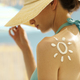 Woman tanning at the beach with sunscreen cream - PhotoDune Item for Sale