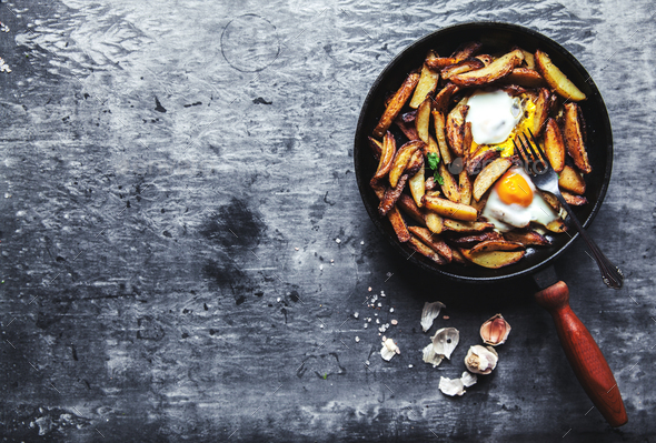 Fried potatoes and eggs in a pan close-up. horizontal - Stock Photo - Images