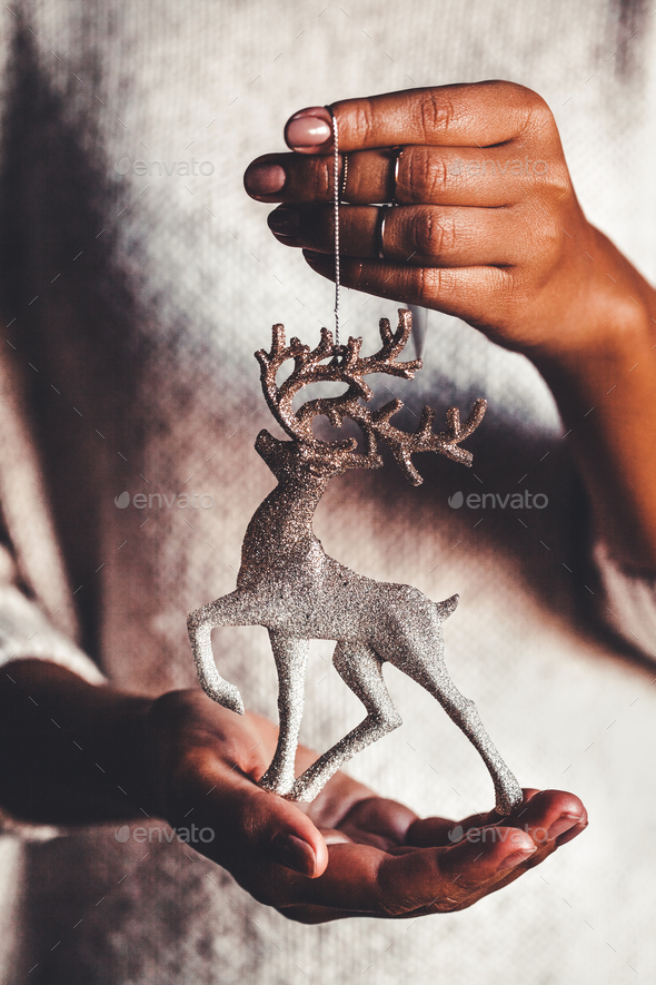 Woman in warm sweater holding toy deer glass decorative ball in hands, copy space. Christmas - Stock Photo - Images