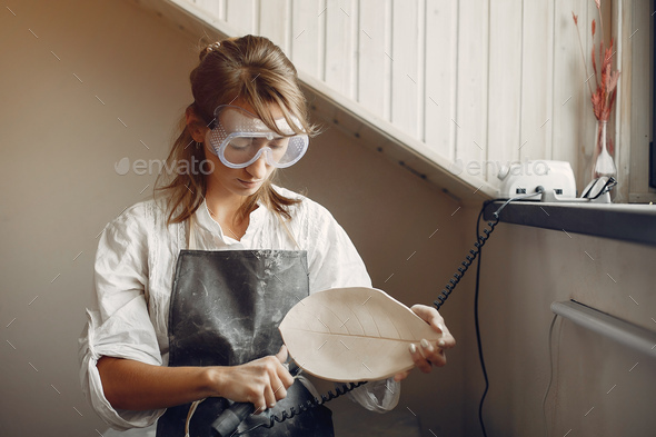 A young woman makes dishes in a pottery - Stock Photo - Images