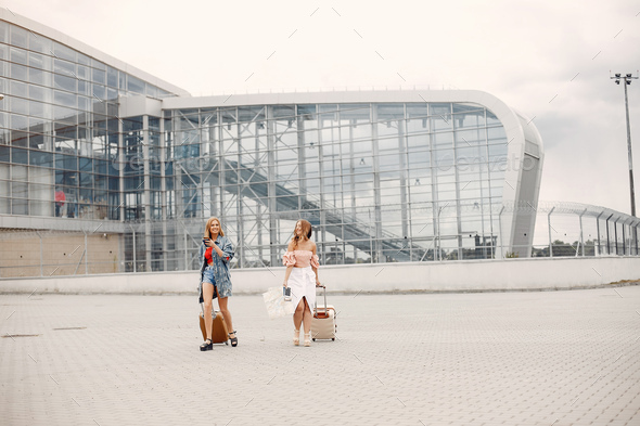 Two beautiful girls standing by the airport - Stock Photo - Images