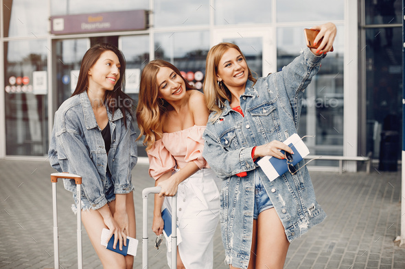 Three beautiful girls standing by the airport - Stock Photo - Images