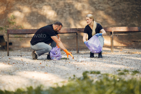 Couple collects garbage in garbage bags in park - Stock Photo - Images