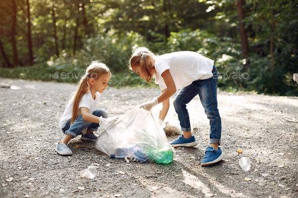 Children collects garbage in garbage bags in park - Stock Photo - Images