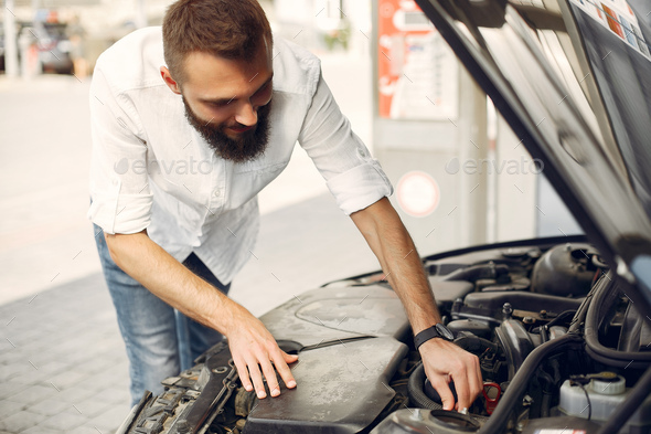 Handsome man checks the engine in his car - Stock Photo - Images