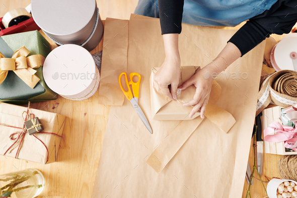Woman using sticky tape when wrapping present - Stock Photo - Images