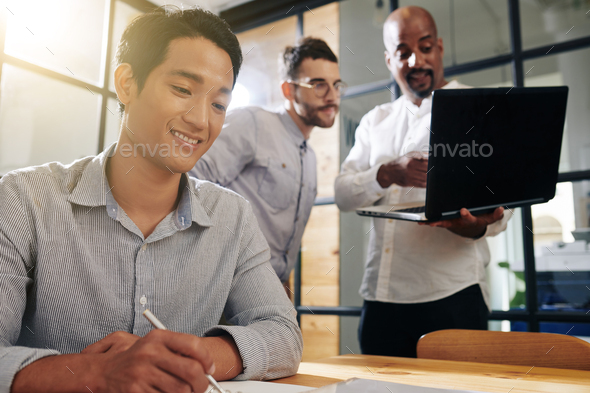 Smiling entrepreneur filling document - Stock Photo - Images