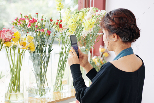 Florist photographing fresh flowers - Stock Photo - Images