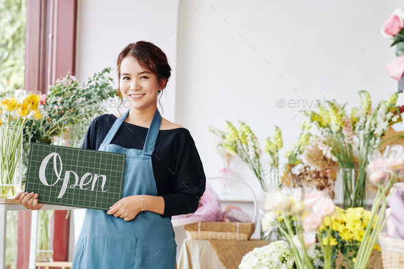 Young Asian woman opening flower shop - Stock Photo - Images