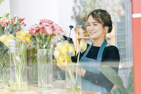 Florist spraying flowers in shop - Stock Photo - Images