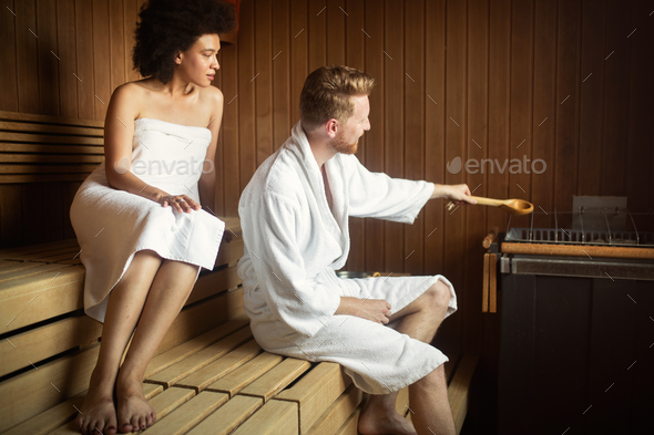 Beautiful couple relaxing in sauna and caring about health and skin - Stock Photo - Images