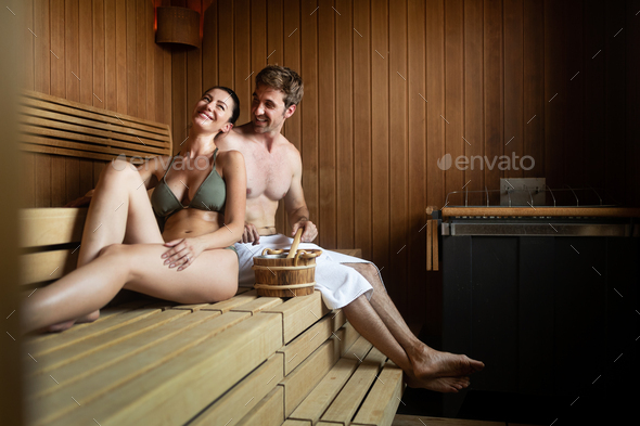 Couple enjoying finnish sauna during their spa weekend - Stock Photo - Images
