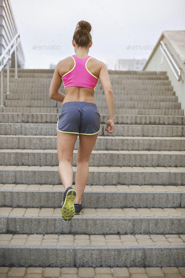 Athletic woman running up the steps - Stock Photo - Images