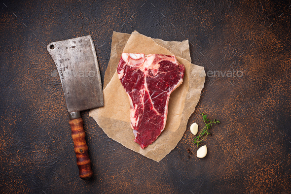 Raw T-bone steak with butchers knife - Stock Photo - Images