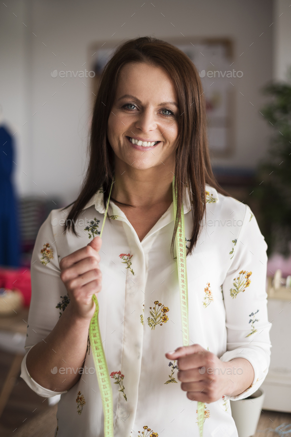 Portrait of beautiful and smiling tailor - Stock Photo - Images