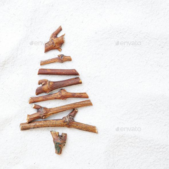 Flat lay stylized Christmas tree made of small twigs on snow bac - Stock Photo - Images