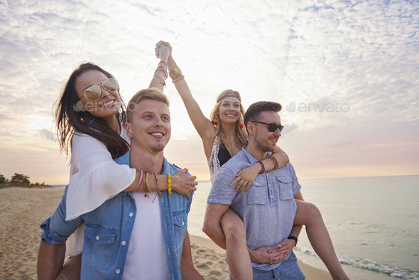 Two girls carried by their boyfriends - Stock Photo - Images