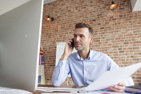 Talking on the phone and analyzing documents - Stock Photo - Images
