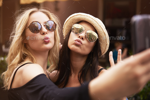 Blonde and dark hair girls taking a selfie - Stock Photo - Images