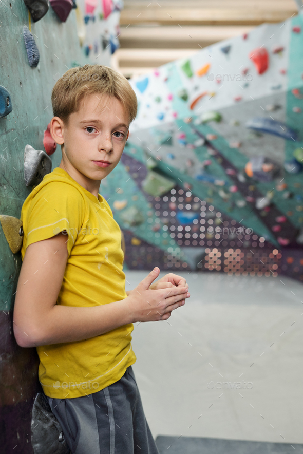 Cute schoolboy in activewear leaning against climbing wall or equipment - Stock Photo - Images