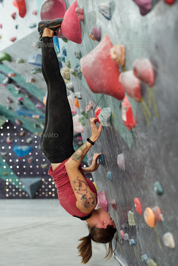 Young skilled sportswoman hanging upside down along climbing wall - Stock Photo - Images