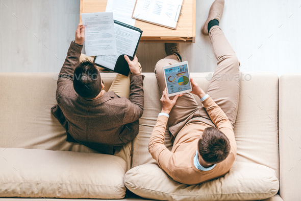 Two young male economists analyzing diagram and looking through financial papers - Stock Photo - Images
