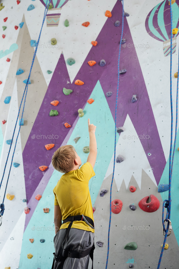 Schoolboy pointing upwards while standing in front of climbing equipment - Stock Photo - Images