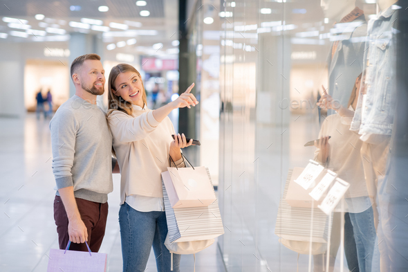 Smiling girl pointing at one of jackets in shop window while talking to man - Stock Photo - Images