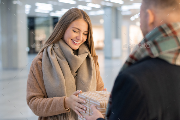 Happy girl looking at giftbox and taking it from her boyfriend hands - Stock Photo - Images