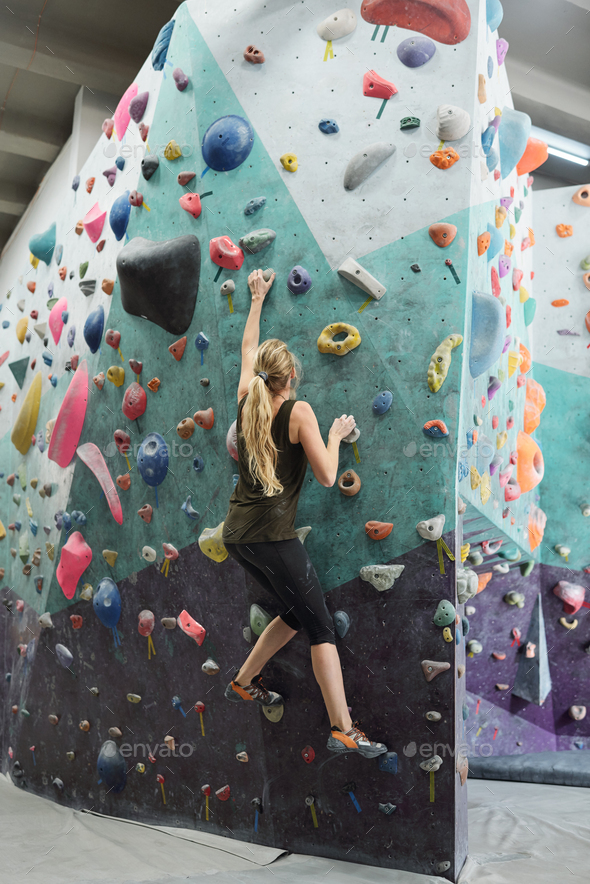 Young active woman with long hair grabbing by artificial rocks on climbing wall - Stock Photo - Images