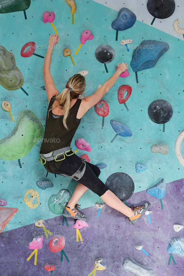 Young woman in climbing equipment moving up while holding by artificial rocks - Stock Photo - Images