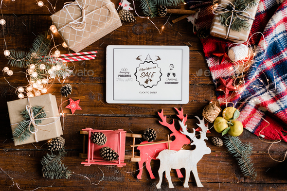 Christmas sale announcement on display of touchpad surrounded by decorations - Stock Photo - Images