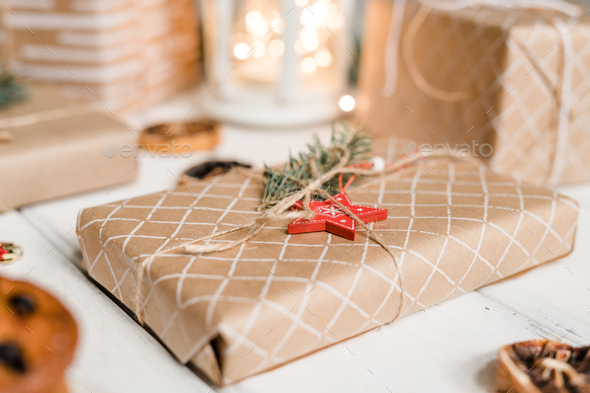 Packed and wrapped giftbox with red star and conifer on top ready for Christmas - Stock Photo - Images