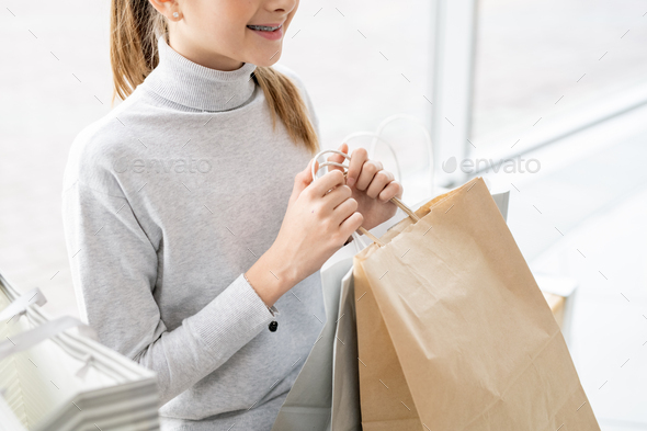 Mid section of cute girl in casualwear holding paperbag with purchase - Stock Photo - Images