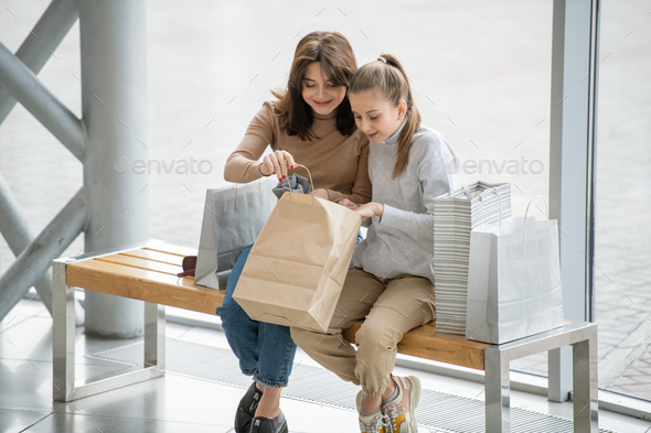 Happy female and her daughter opening paperbag and looking at what they bought - Stock Photo - Images